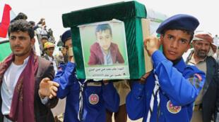 Exploradores llevan el ataúd de un niño durante el funeral de las personas asesinadas en un ataque aéreo de la coalición encabezado por Arabia Saudí en un autobús en el norte de Yemen, en Saada. 13 de agosto de 2018.