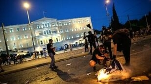 Protesters burn a Greek flag in central Athens during an anti-austerity protest on July 15, 2015.