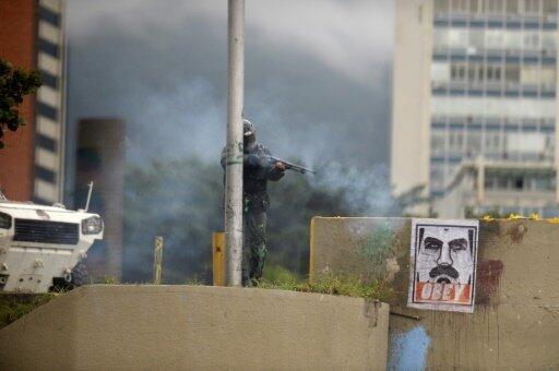 عنصر من شرطة مكافحة الشغب يطلق الرصاص المطاطي على المتظاهرين - كراكاس في 7 يونيو 2017