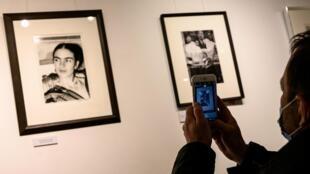 Un visiteur de la Galerie de l'instant photographie le 6 février 2021 à Paris un portrait de l'artiste mexicaine Frida Kahlo, immortalisée par la photographe américaine Lucienne Bloch