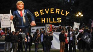 La gente protesta en Beverly Hills a pocos kilómetros donde el presidente de los Estados Unidos, Donald Trump, llevó a cabo una recaudación de fondos en California, Estados Unidos, el 13 de marzo de 2018