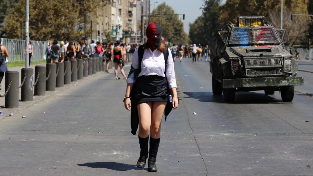 Una mujer camina junto a un vehículo de la policía antidisturbios durante una huelga de mujeres como parte de las actividades del Día Internacional de la Mujer en Santiago, Chile, 9 de marzo de 2020.