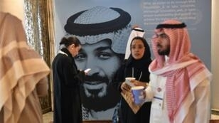 Misk Global Forum attendees mingle in front of a portrait of Saudi Crown Prince Mohammed bin Salman in Riyadh on November 14, 2018