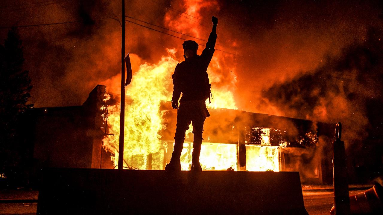 Un joven se eleva en una plataforma y levanta el puño, mientras un comercio está envuelto en llamas, en la cuarta jornada de protestas, el 30 de mayo de 2020, en Minneapolis, Minnesota (Estados Unidos).