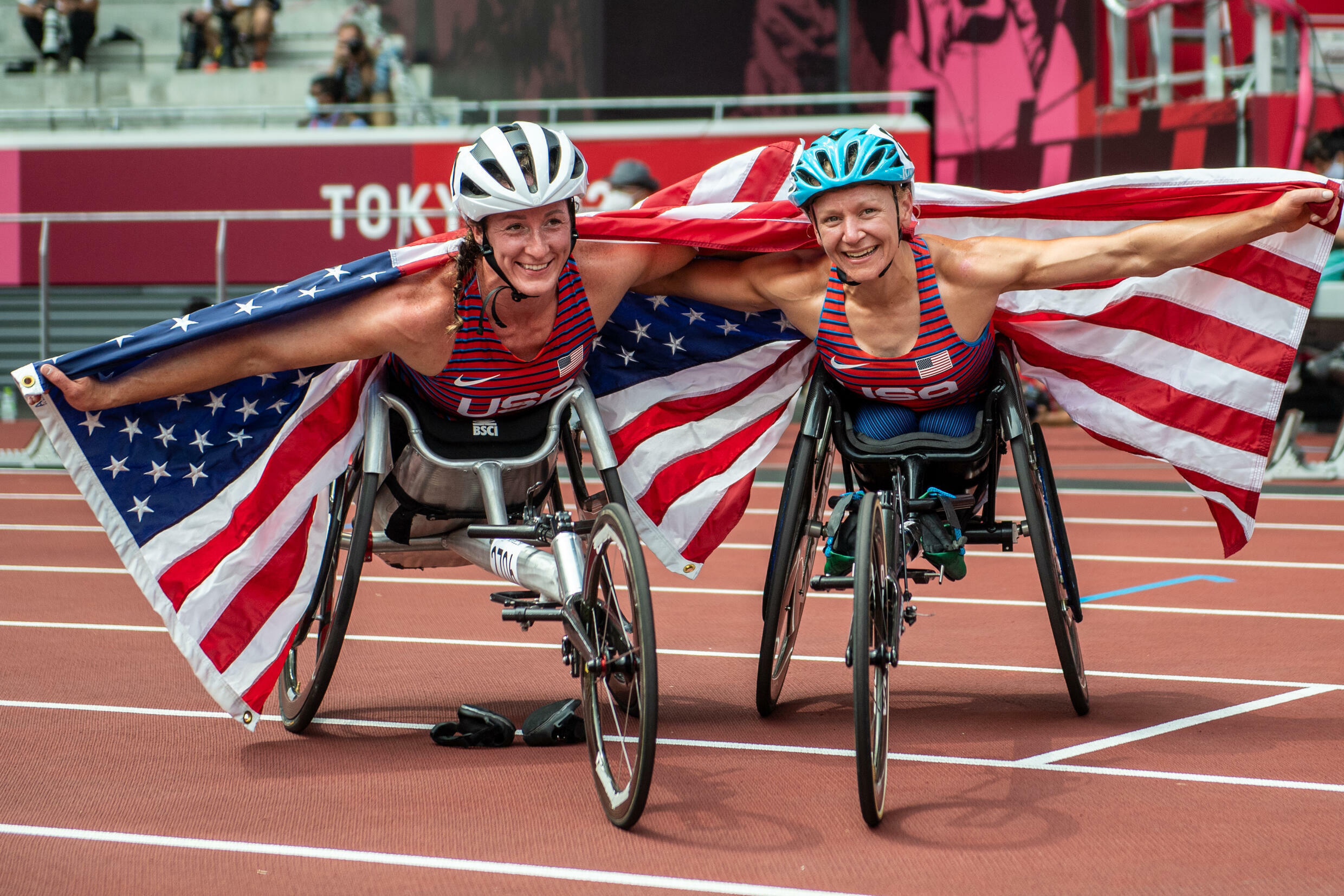 Tatyana McFadden (L) and Susannah Scaroni celebrate after winning bronze and gold in the women's 5,000m T54 respectively