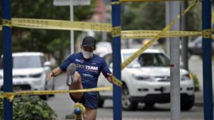 Un hombre hace ejercicio con una máscara facial en un parque público de Bogotá durante la pandemia del coronavirus, el 5 de mayo de 2020