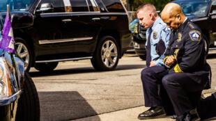 File photo taken June 4, 2020 of Minneapolis Police Chief Medaria Arradondo (R) kneeling as the remains of George Floyd are taken to a memorial service in Minneapolis, USA.