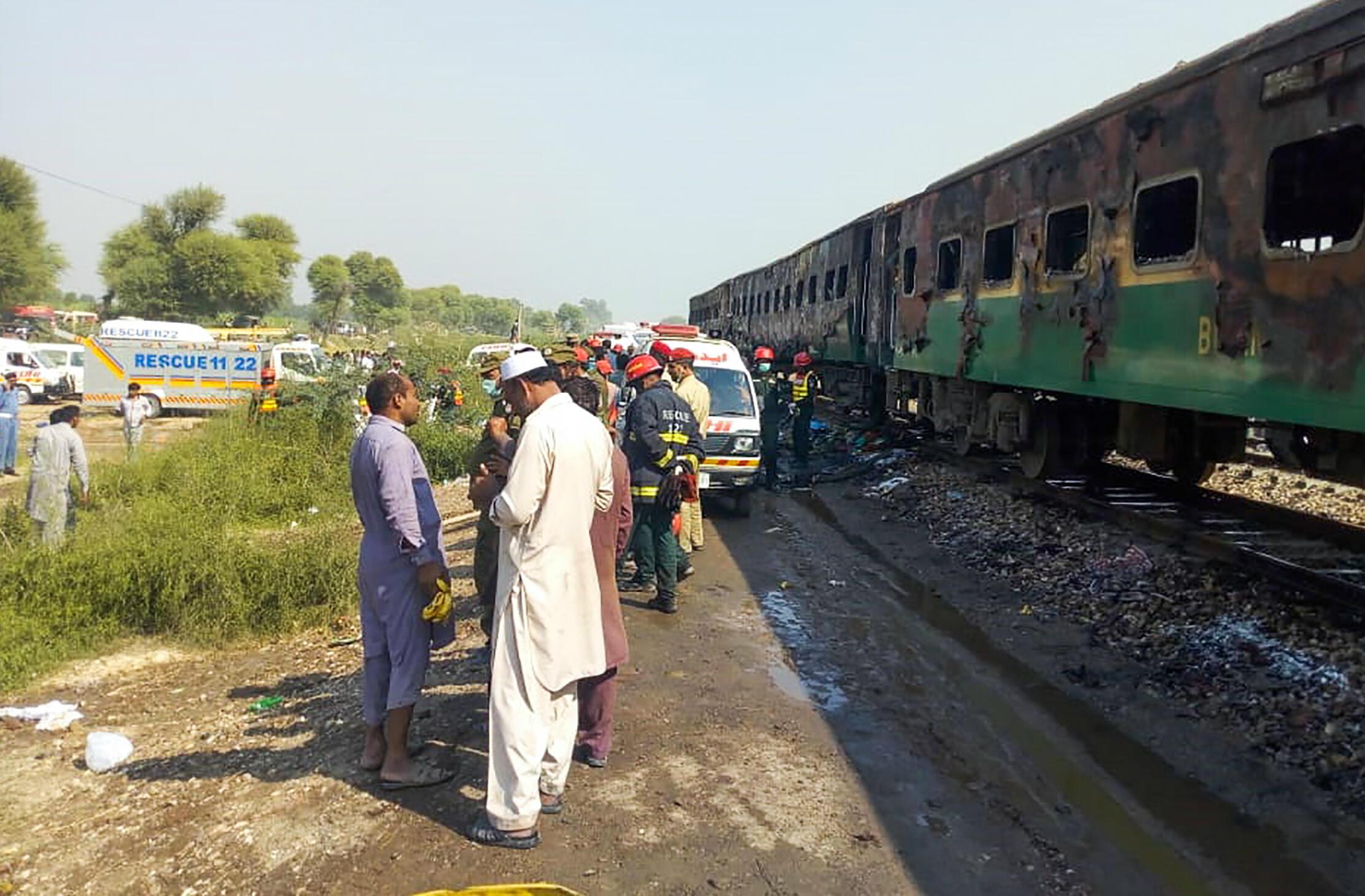 Des passagers se rassemblent en dehors d'un train, en feu après l'explosion d'une bonbonne de gaz, le 31 octobre près de Rahim Yar Khan, au Pakistan.