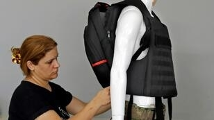 An employee of the Israeli protection gear manufacturer Masada Armour adjusts a new civilian bulletproof backpack, designed for schoolchildren, at the company's headquarters in Julis, northern Israel