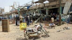 يمنيون قرب حافلة دمرت في موقع ضربة جوية في 10 آب/أغسطس للتحالف العربي بصعدة قبل يوم.