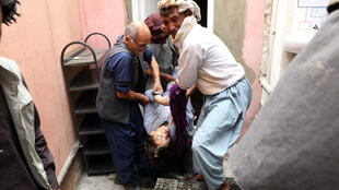 Men carry the dead body of a woman following a suicide attack on a maternity hospital in Kabul