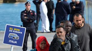 Migrantes a punto de subirse en un ferry, en el puerto de la isla italiana de Lampedusa, para ser transferidos a Porto Empedocle, en Sicilia, el 18 de febrero de 2015.