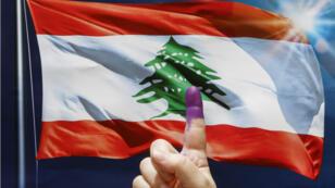 Une femme brandit son index taché d'encre après avoir voté à Beyrouth, le 6 mai 2018.