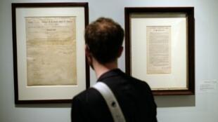 """زائر يتأمل الوثيقتين في مزاد لدار """"سوذبيز"""" في نيويورك في 18 أيار/مايو 2016"""