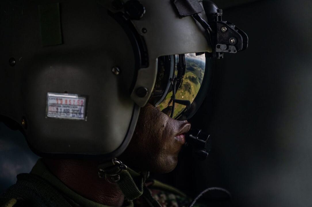 Un militar a bordo de un helicóptero del Ejército. Estas aeronaves patrullan y abastecen a las tropas de tierra de la Operación Artemisa, que pueden pasar meses en la selva antes de ser relevadas. El personal militar es la única presencia, ocasional, del Estado colombiano en estas zonas remotas en las que son grupos armados, algunos de ellos disidencias de la exguerrilla de las FARC, los que tienen el control sobre los pobladores.