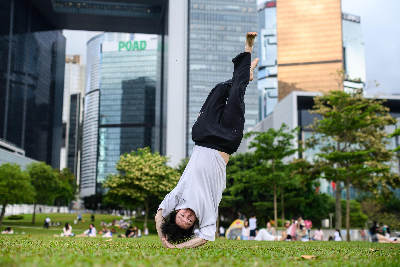 Un hombre se ejercita sobre el césped en el Parque Tamar de Hong Kong, el 5 de mayo de 2020.