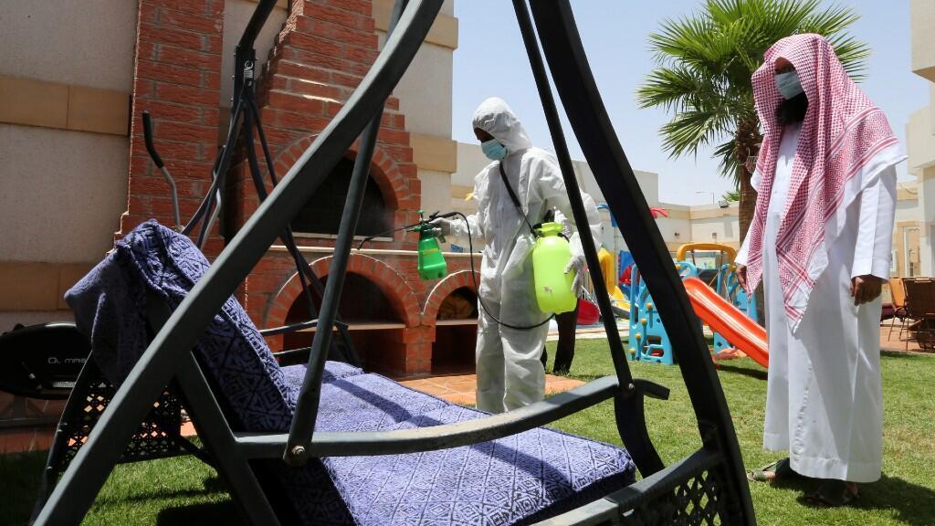 Un trabajador con traje de protección esteriliza un banco antes de que lo usen las familias saudíes, después de que el gobierno levantara las restricciones de cierre de la enfermedad coronavirus (COVID-19), en Riad, Arabia Saudita, el 6 de julio de 2020.