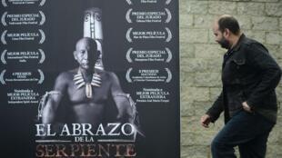 """El director colombiano Ciro Guerra ante un poster de su película """"El abrazo de la serpiente"""", en enero de 2016 en Bogotá"""