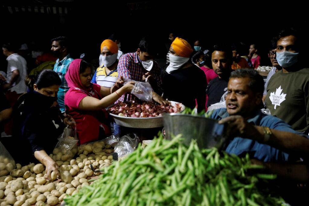Gente comprando verduras en un mercado después de que el primer ministro de India, Narendra Modi, pidiera un cierre nacional a partir de la medianoche para limitar la propagación del coronavirus. Nueva Delhi, India. 24 de marzo de 2020.