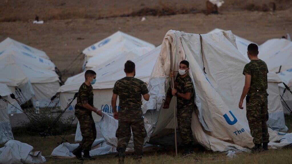 varios militares griegos instalan tiendas de campaña de ACNUR en un campo de tiro de la isla de Lesbos, en Grecia, el 11 de septiembre de 2020.