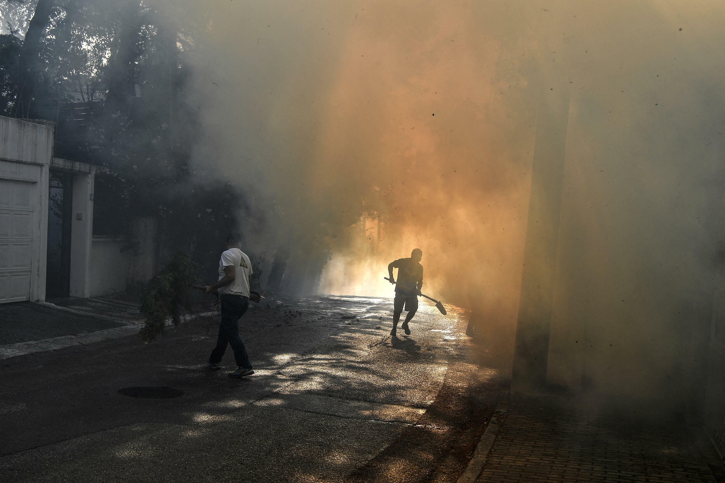 A local resident runs to fight a fire in Thrakomakedones, near Mount Parnitha, north of Athens, on August 7, 2021.