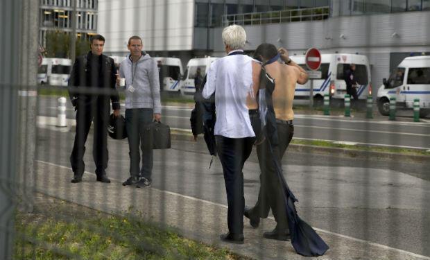 Broseta, shirtless, walk away from demonstrators, accompanied by anti-riot police officers