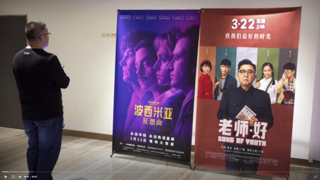 """Un espectador chino mira un póster de la película """"Bohemian Rhapsody"""" en un cine en Beijing, China, el 27 de marzo de 2019."""