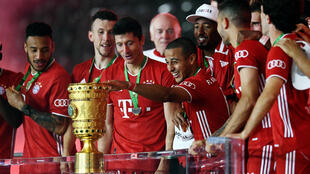Thiago Alcantara touches the German Cup trophy after Bayern Munich's 4-2 triump over Bayer Levekursen in Saturday's German Cup final.