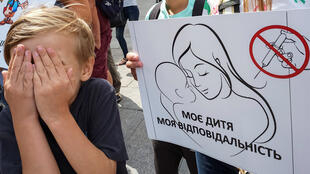 """A boy attends a protest by anti-vaccination activists in Kiev, Ukraine, August 22, 2019. The banner reads: """"My baby is my responsibility""""."""