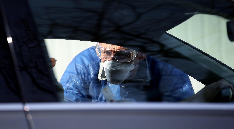 Un doctor toma una muestra de un conductor en un centro de detección del coronavirus instalado en un aparcamiento en Halle, Alemania, el 27 de marzo de 2020