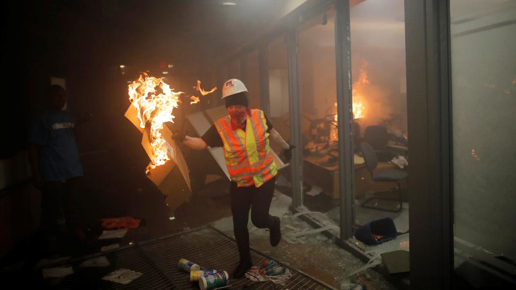 Una manifestante corre con un cartón ardiendo, en la entrada de una estación de policía incendiada en Mineápolis, Minnesota (Estados Unidos).