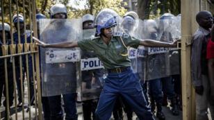 La police anti-émeute zimbabwéenne ferme la porte des Rainbow Towers, où les résultats des élections ont été annoncés, alors que les partisans du Mouvement pour le changement démocratique (MDC) protestent.