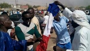Anti-Charlie Hebdo protesters burn a French flag in the city of Zinder, Niger, on January 16 2015