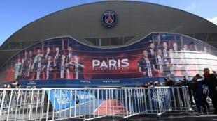 Des spectateurs près des barrières mises en place pour empêcher le contact entre les joueurs et les supporters au Parc des Princes à Paris, le 29 février avant le match de Ligue1 PSG-Dijon.
