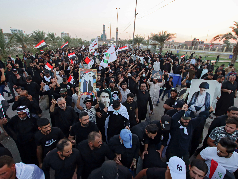 أنصار رجل الدين العراقي مقتدى الصدر يحملون ملصقات عليها صورته في مدينة النجف الشيعية في 27 آب/أغسطس 2021 لإظهار دعمهم لقراره بالمشاركة في انتخابات تشرين الأول/أكتوبر