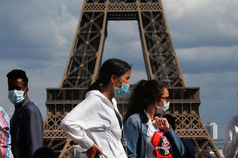 Des personnes portant un masque au Trocadéro, en face de la Tour Eiffel, à Paris, le 3 août 2020.
