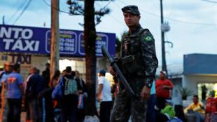 Un soldado del Ejército de Brasil patrulla en una calle junto a un grupo de venezolanos después de verificar sus pasaportes o documentos de identidad en el control fronterizo de Pacaraima , estado de Roraima, Brasil, el 19 de agosto de 2018.