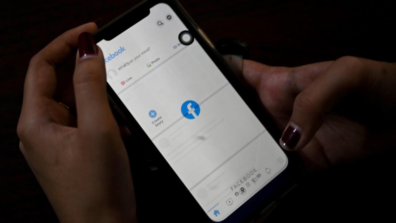 Una mujer utiliza su teléfono móvil para consultar Facebook en Yangon el 4 de febrero de 2021, cuando los generales de Myanmar ordenaron a los proveedores de Internet que restringieran el acceso a Facebook, días después de tomar el poder.