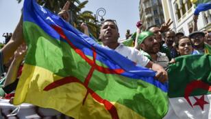Des manifestants algériens agitent le drapeau national et un étendard amazigh lors de la manifestation hebdomadaire du vendredi à Alger, le 21 juin 2019.