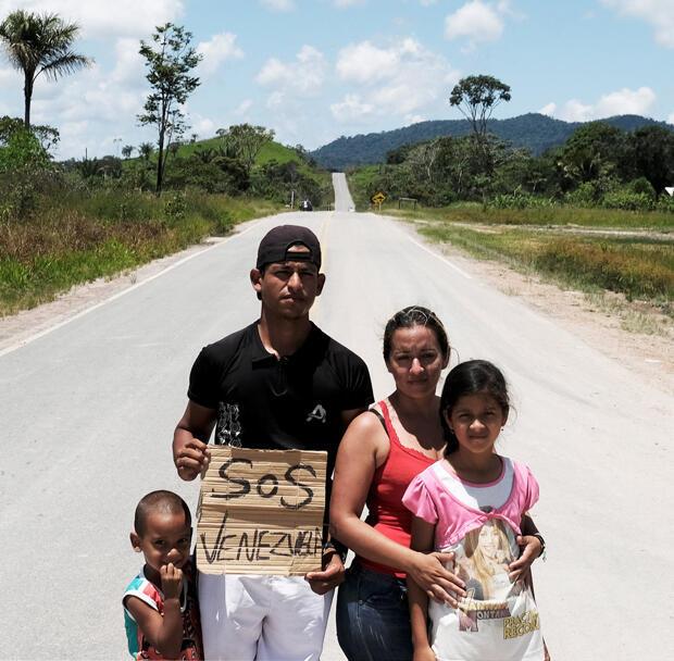 Una familia venezolana posa para una foto mientras intentan hacer autostop hacia la ciudad de Boa Vista, luego de obtener el estatus de refugiado a través de la Policía Federal en el control fronterizo de Pacaraima.