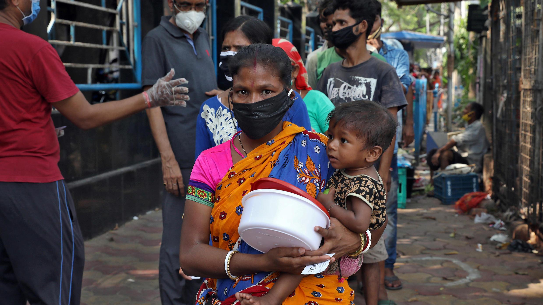 Una mujer sin hogar que sostiene a un niño espera recibir alimentos durante un encierro nacional de 21 días para frenar la propagación de la enfermedad coronavirus (COVID-19) en Calcuta, India, el 3 de abril de 2020