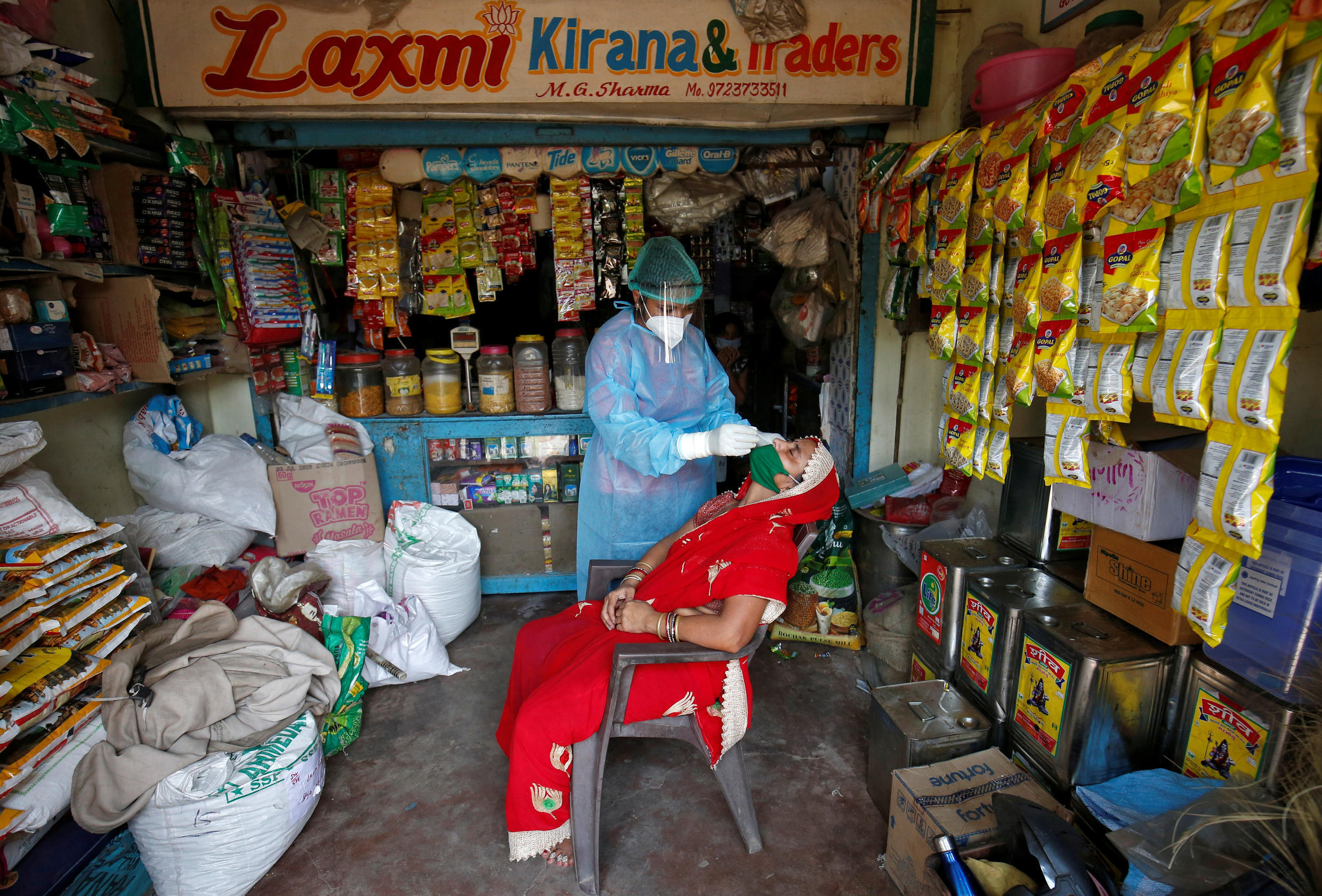A healthcare worker wearing personal protective equipment takes a swab from a woman for a rapid antigen test inside her grocery shop, amid the coronavirus disease outbreak, in Ahmedabad, India, September 4, 2020.