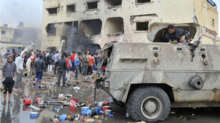 An Egyptian man stands in an armoured vehicle as residents gather outside a police station in North Sinai's provincial capital of al-Arish after it was targeted by a car bomb on April 12, 2015.