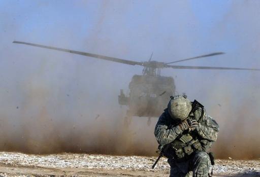 جندي يحمي وجهه من غبار المروحية خلال عملية للقوات الاميركية في العراق في 2010