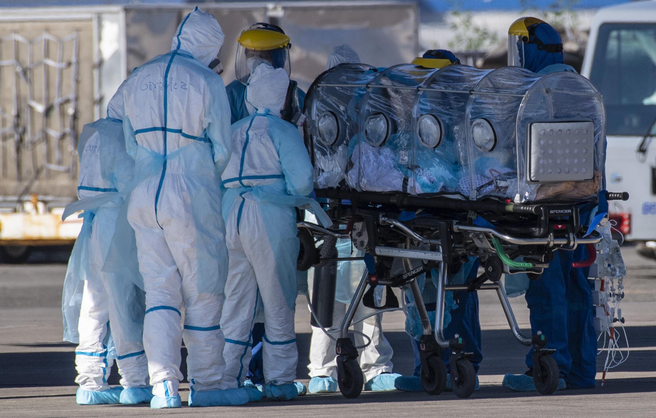 Trabajadores de la salud trasladan a un paciente infectado de Covid-19 a un Hércules C-130, en una base de la Fuerza Aérea Chilena en Santiago, Chile, el 24 de mayo de 2020.