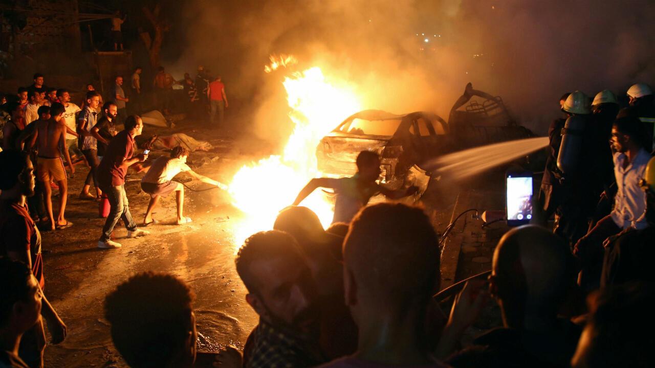 Las personas extinguen un incendio producto de una explosión afuera del Instituto Nacional del Cáncer en El Cairo, Egipto, el 4 de agosto de 2019.