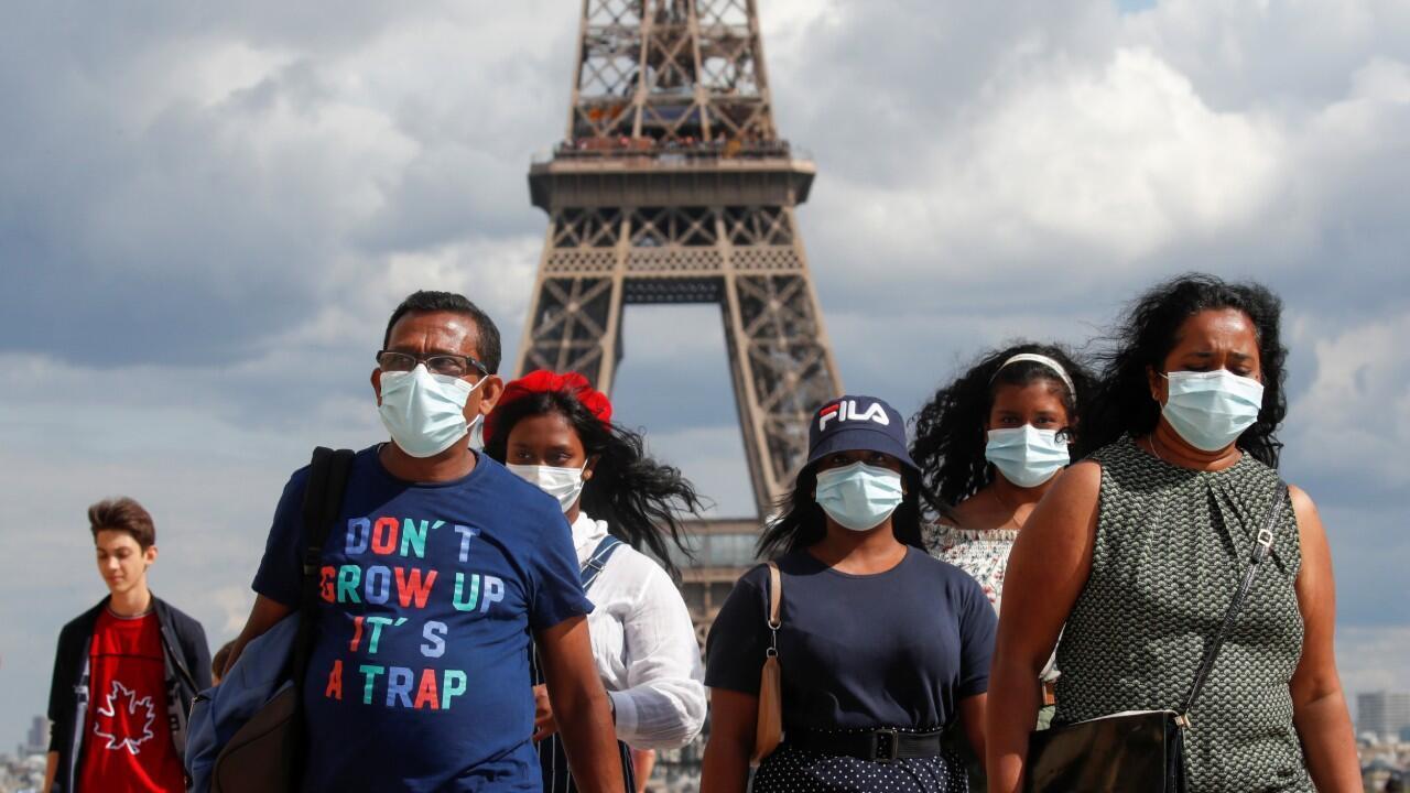 Las personas con máscaras protectoras caminan en la plaza Trocadero cerca de la Torre Eiffel en París el 3 de agosto de 2020.