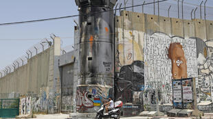 A mural painting of US President Donald Trump on Israel's controversial separation barrier in the West Bank city of Bethlehem