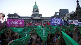 Manifestantes sostienen pañuelos verdes frente al Congreso argentino para reclamar por la legalización del aborto legal, seguro y gratuito, en Buenos Aires, el 19 de febrero de 2019.