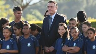 Brazilian President Jair Bolsonaro, seen during a May 21, 2019 event with a school group in Brasilia, has defended the practice of child labor though it is banned in his country